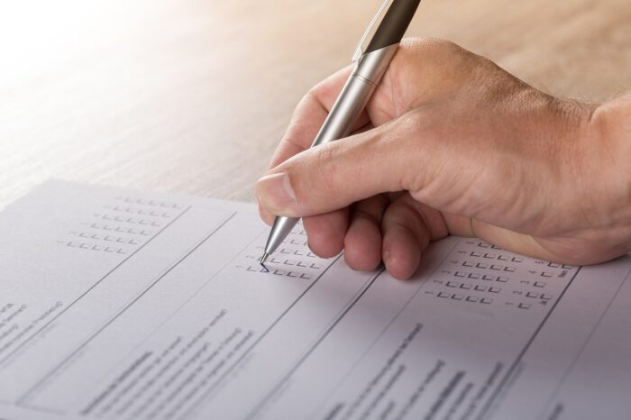 Grafika do artykuły - arkusz z dłonią i długopisem